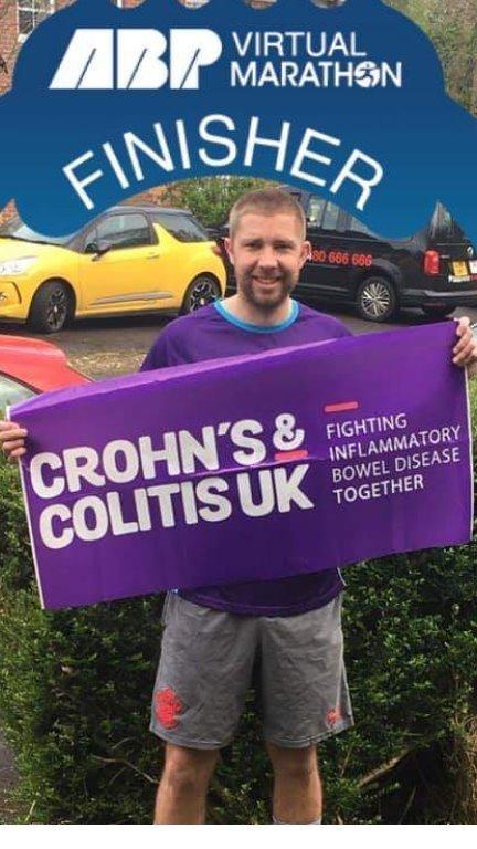 marathon finisher holding Crohn's & Colitis UK banner