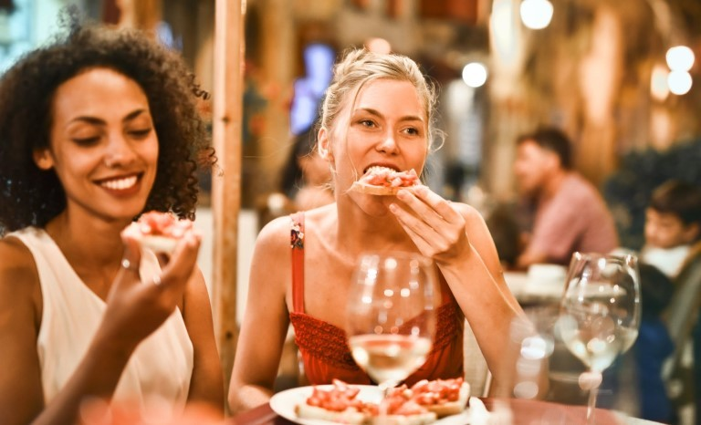 friends eating pizza in a restaurant