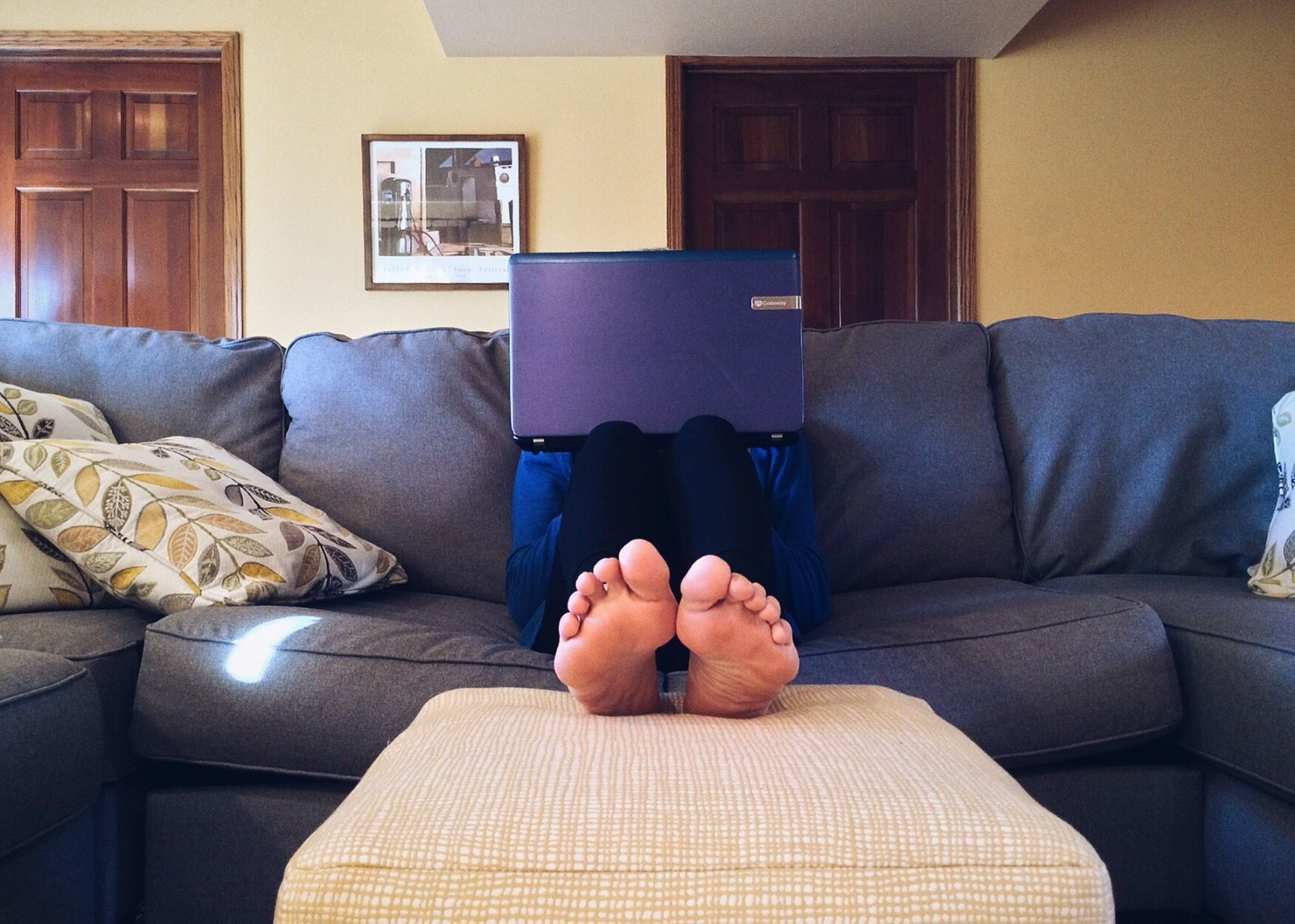 person sat on the sofa with laptop on their lap